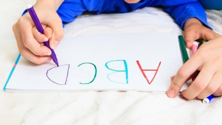 mother holding toddlers hand drawing abcs